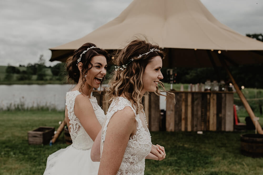 Gem & Kara walking past a Nimbus Tipi on their wedding day