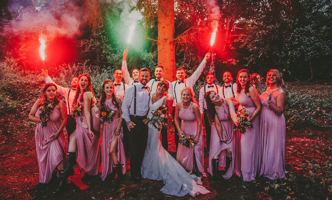 Adele & Paul on their wedding day in the woodland being lit by flares