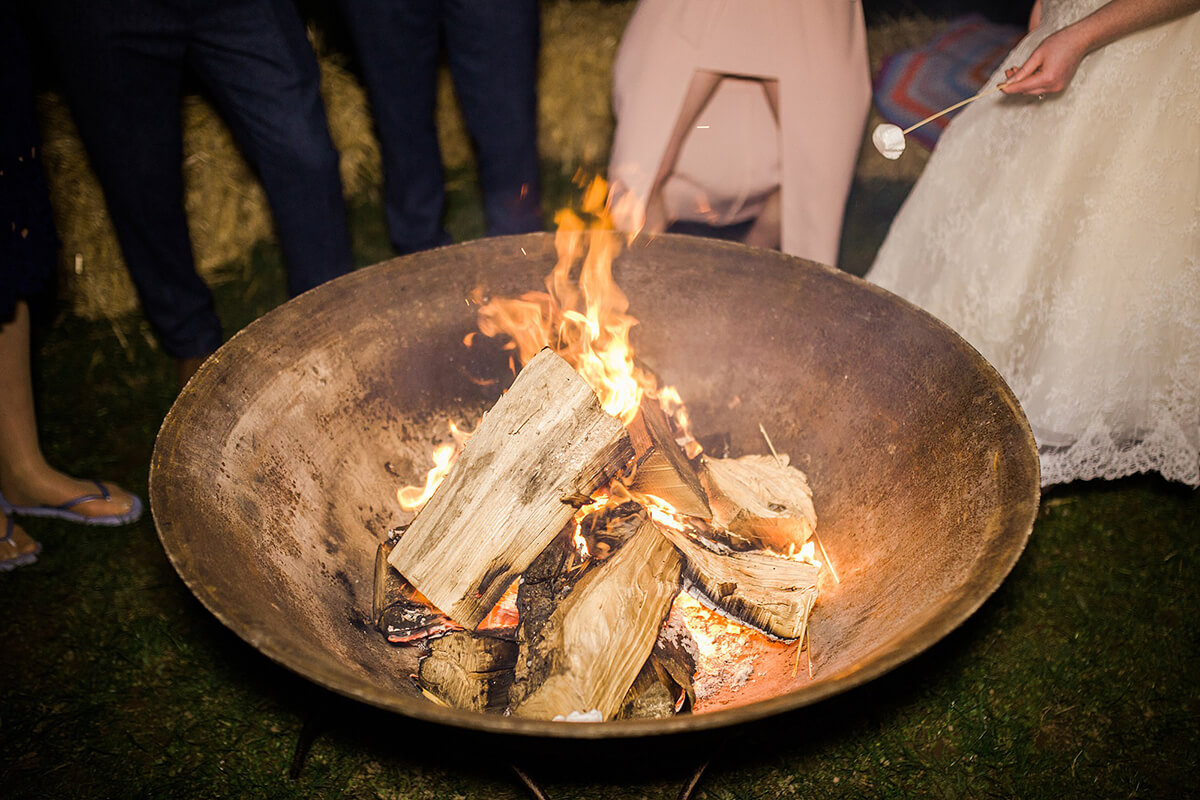 Outdoor fire bowl cooking marshmallows over it at a tipi wedding