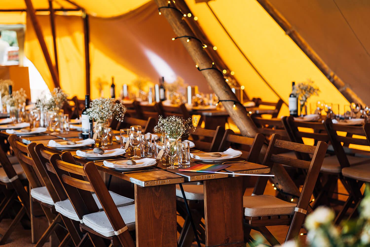 Rustic tables and folding wooden chairs in our Tipis