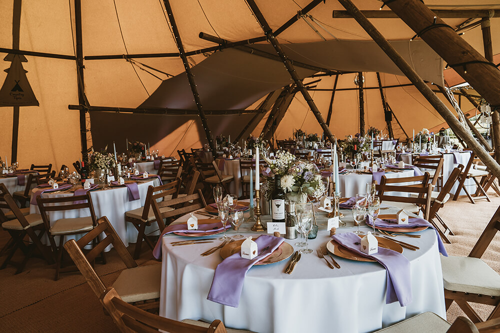 Round tables and folding wooden chairs inside the Tipis