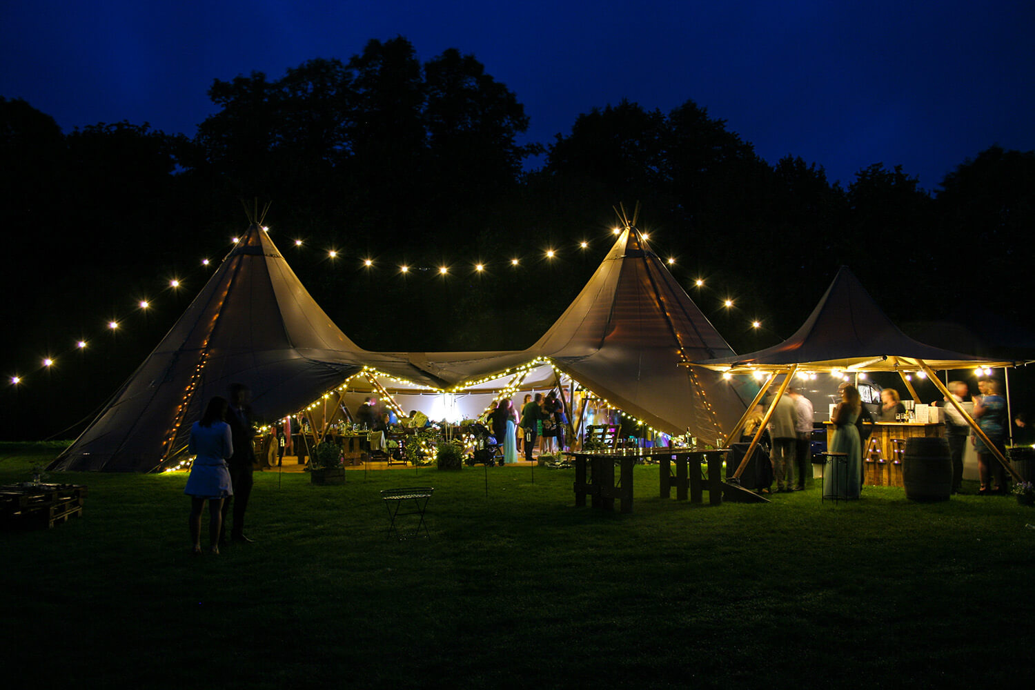 Two Tipis with festoon lighting and a nimbus with a bar beneath