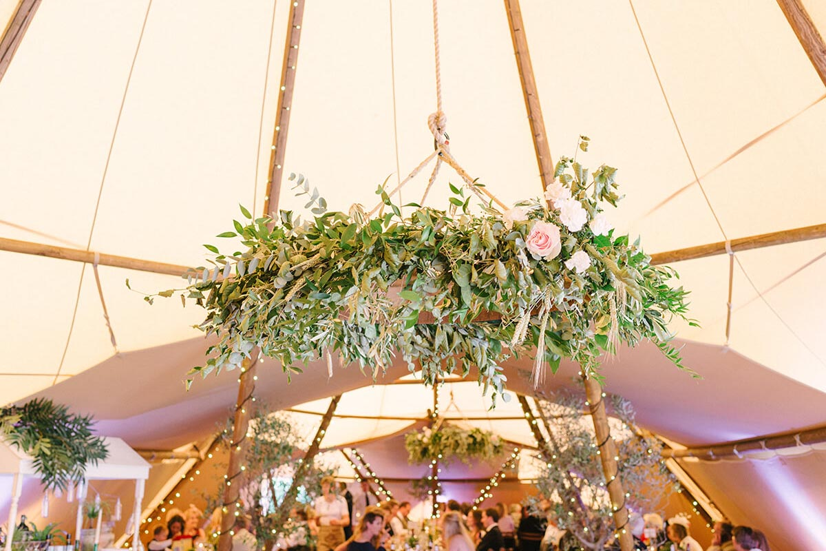 Flower ring inside a giant tipi at an outdoor wedding